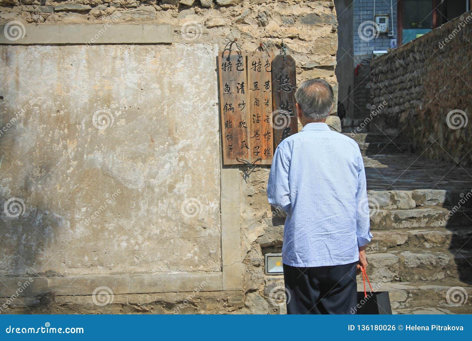 Un uomo anziano che legge il segno