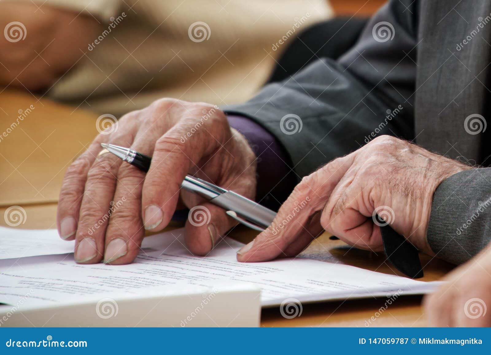 Un uomo anziano scrive una penna nel questionario Vecchiaia ed imparare Disoccupazione e pensionamento