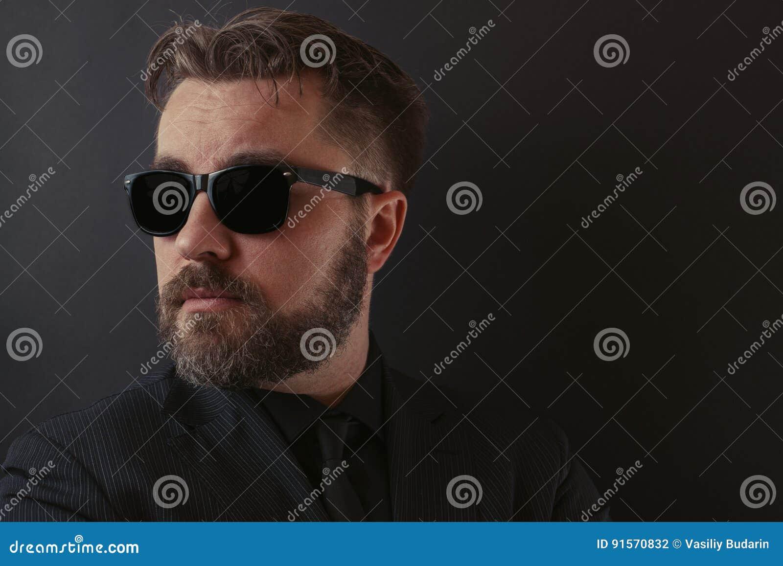 Un uomo brutale con una barba e una pettinatura alla moda in vestito nero ed occhiali da sole