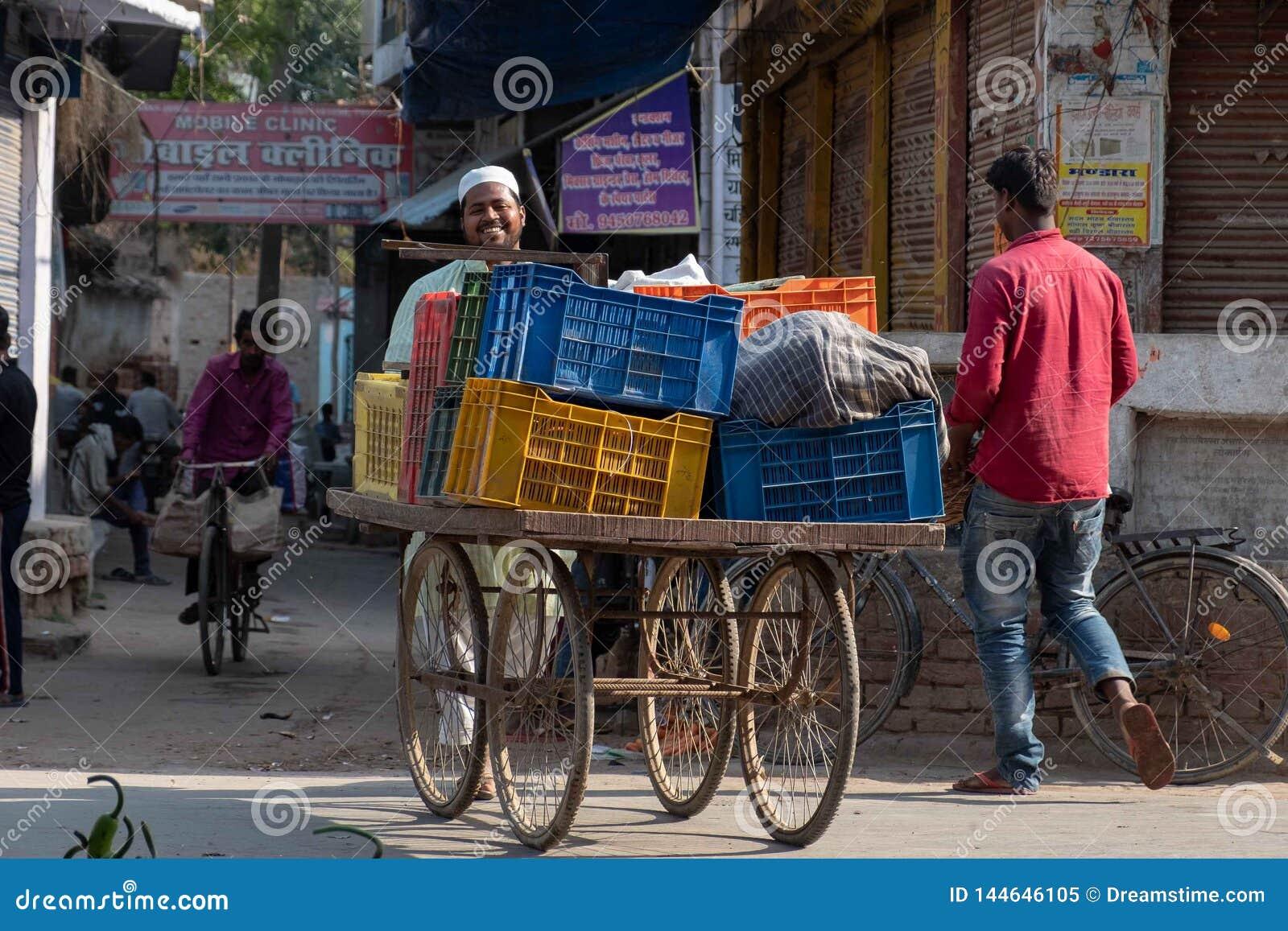 Un uomo cammina un carretto delle verdure alla stalla della sua famiglia in Bhadarsa