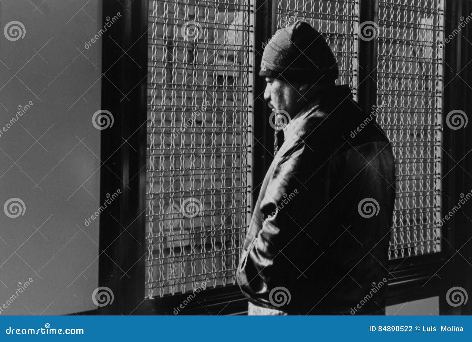 Un uomo che fissa fuori alla stazione ferroviaria in Jackson Heights