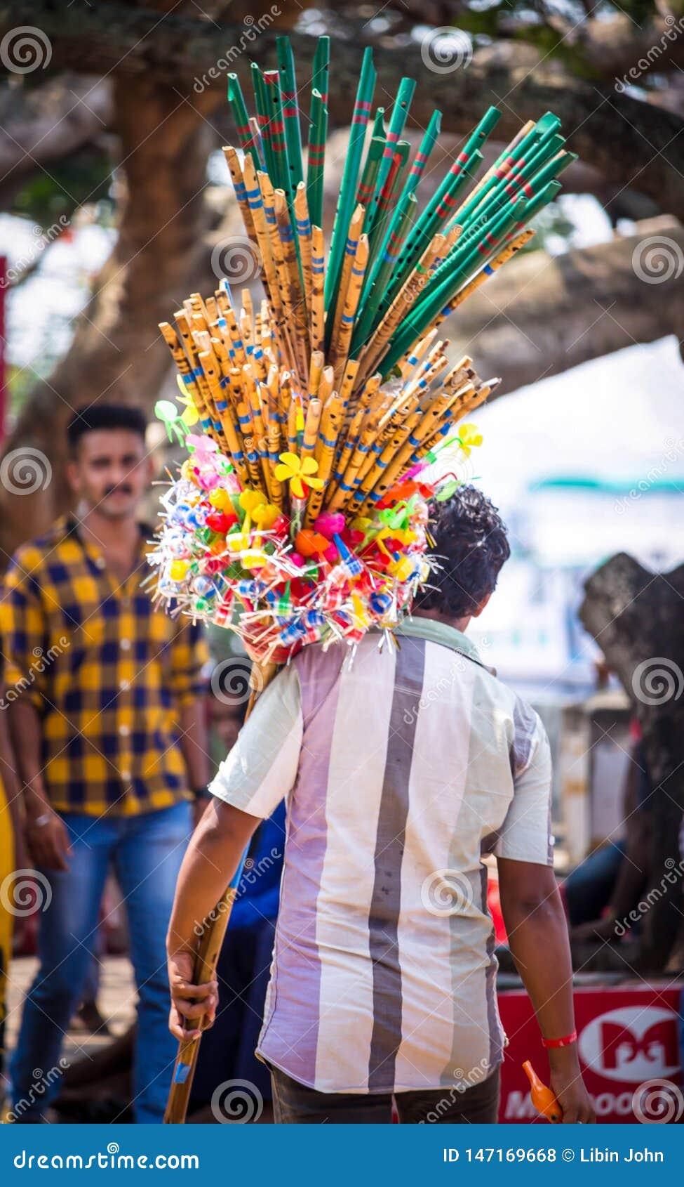 Un uomo che vende le flauto di bambù in via