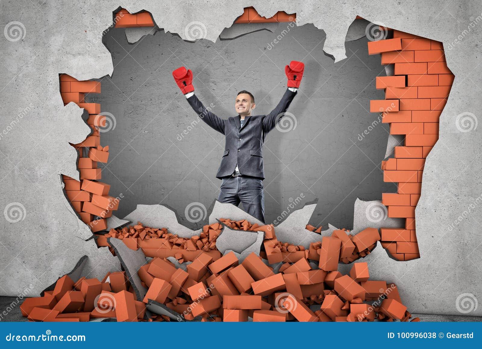 Un uomo d affari vittorioso in guantoni da pugile sta vicino ad un foro in un muro di mattoni con macerie che si trovano intorno