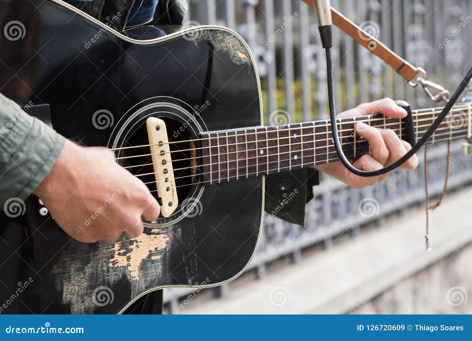 Un uomo della corsa mista che gioca chitarra nella via