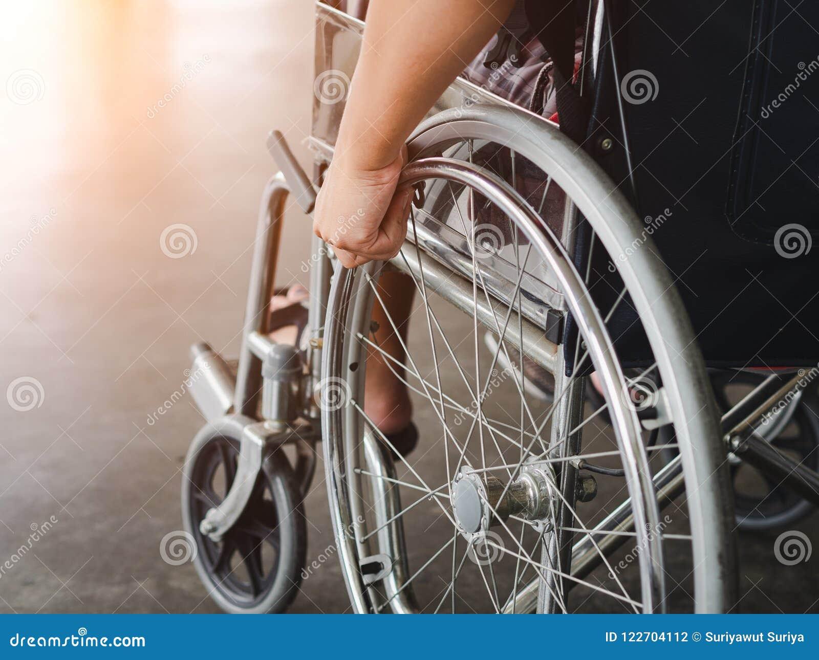 Un uomo disabile sta sedendosi in una sedia a rotelle Tiene le sue mani sopra