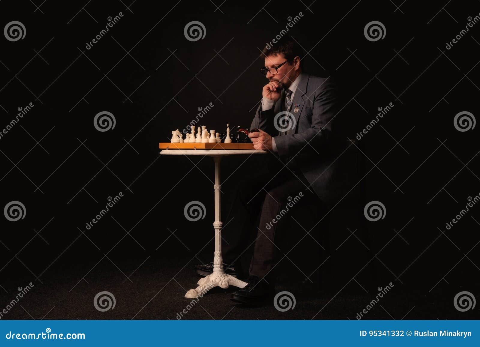 Un uomo gioca gli scacchi e fuma un tubo su un fondo scuro