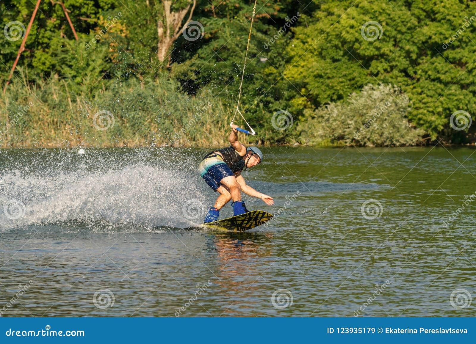 Un uomo impegnato in wakeboard sul lago esegue i salti