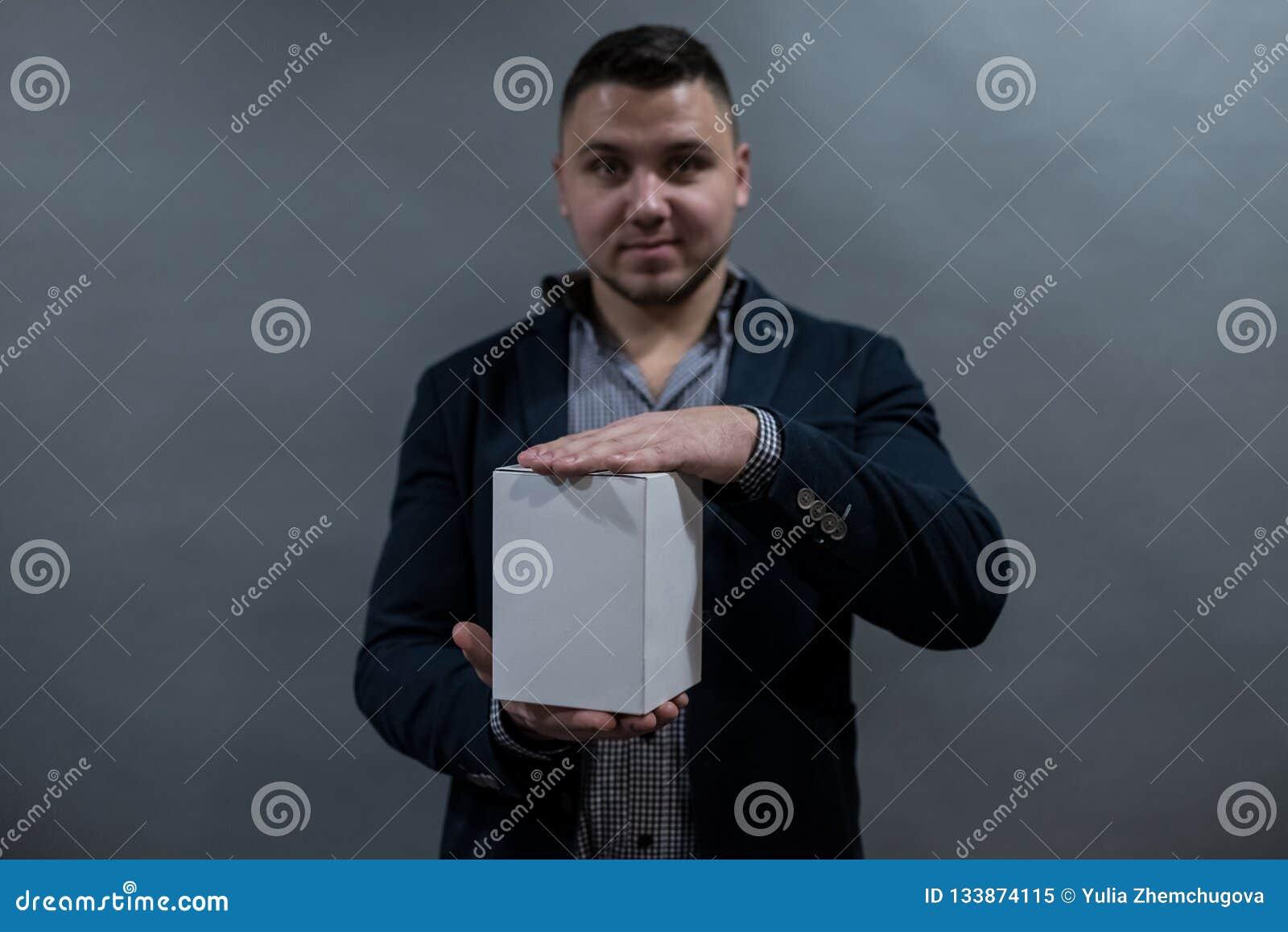 Un uomo in un rivestimento ed in una camicia che tengono un contenitore di Libro Bianco