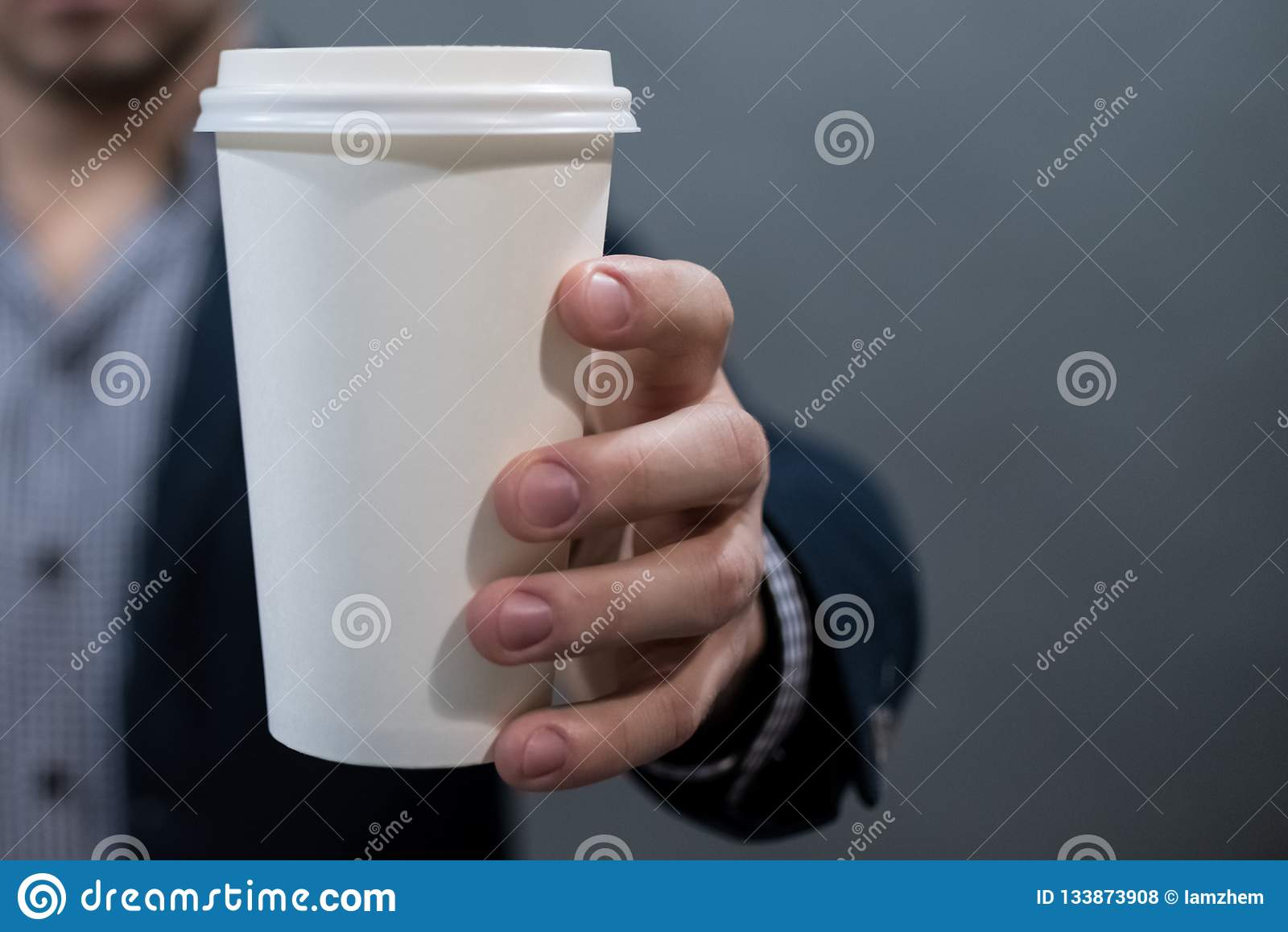 Un uomo in un rivestimento ed in una camicia che tengono una tazza di Libro Bianco bianco in bianco per il vostro testo