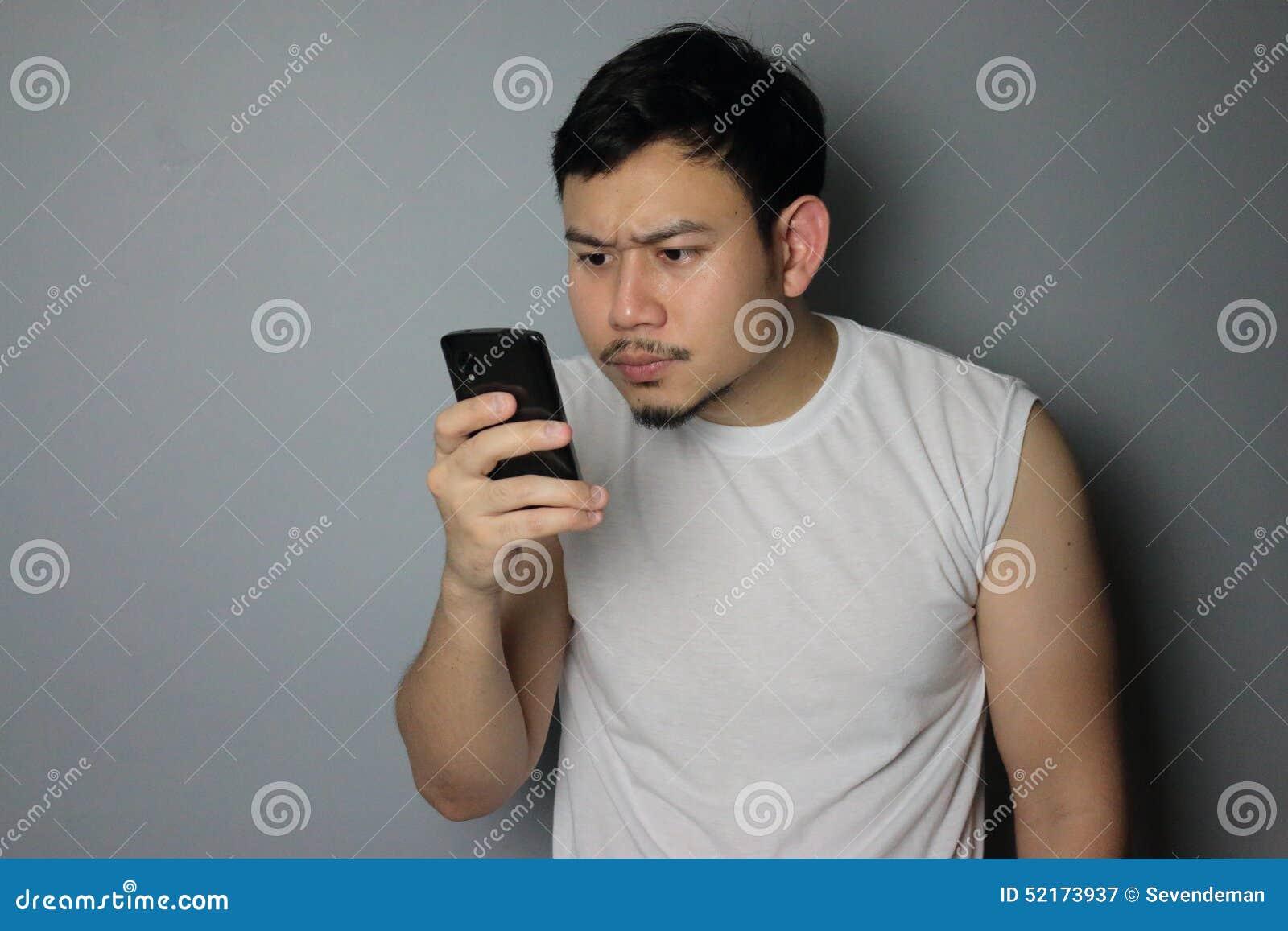 Un uomo sta considerando il telefono cellulare