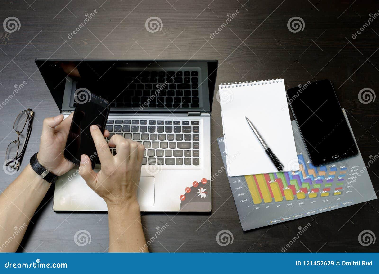 Un uomo stampa su un computer portatile, trovantesi accanto al telefono, glasse della compressa