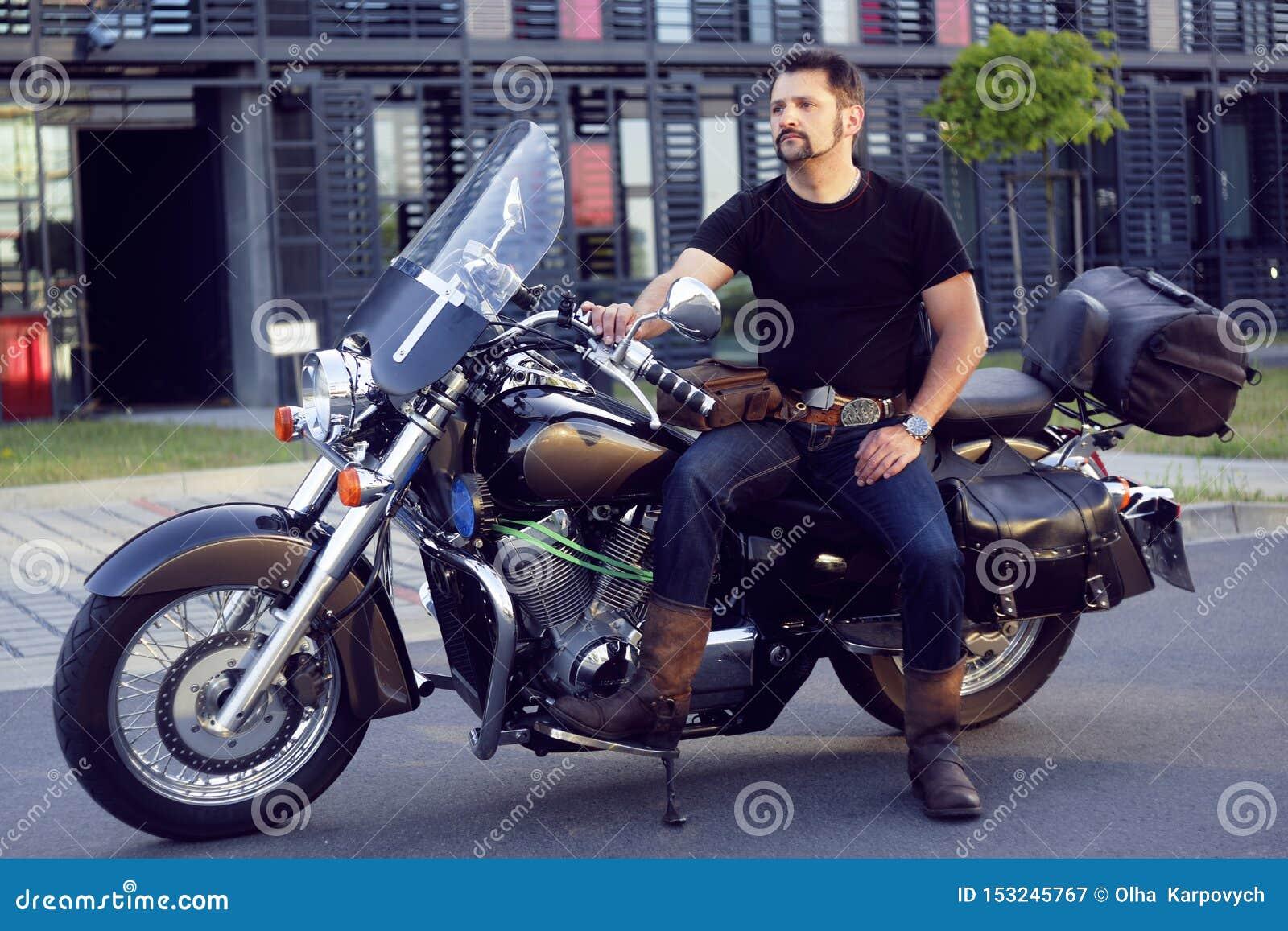 Un uomo su un motociclo vicino all ufficio L uomo su un motociclo prende la sua amica da lavoro Il motociclista è venuto a lavora
