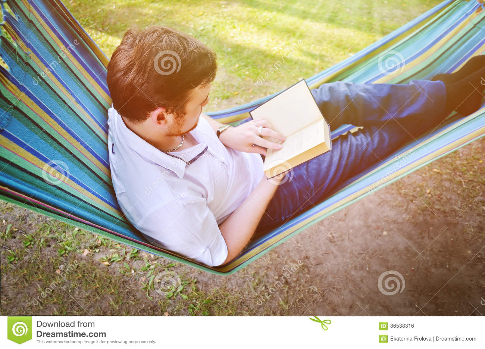 Un uomo in un amaca legge un libro
