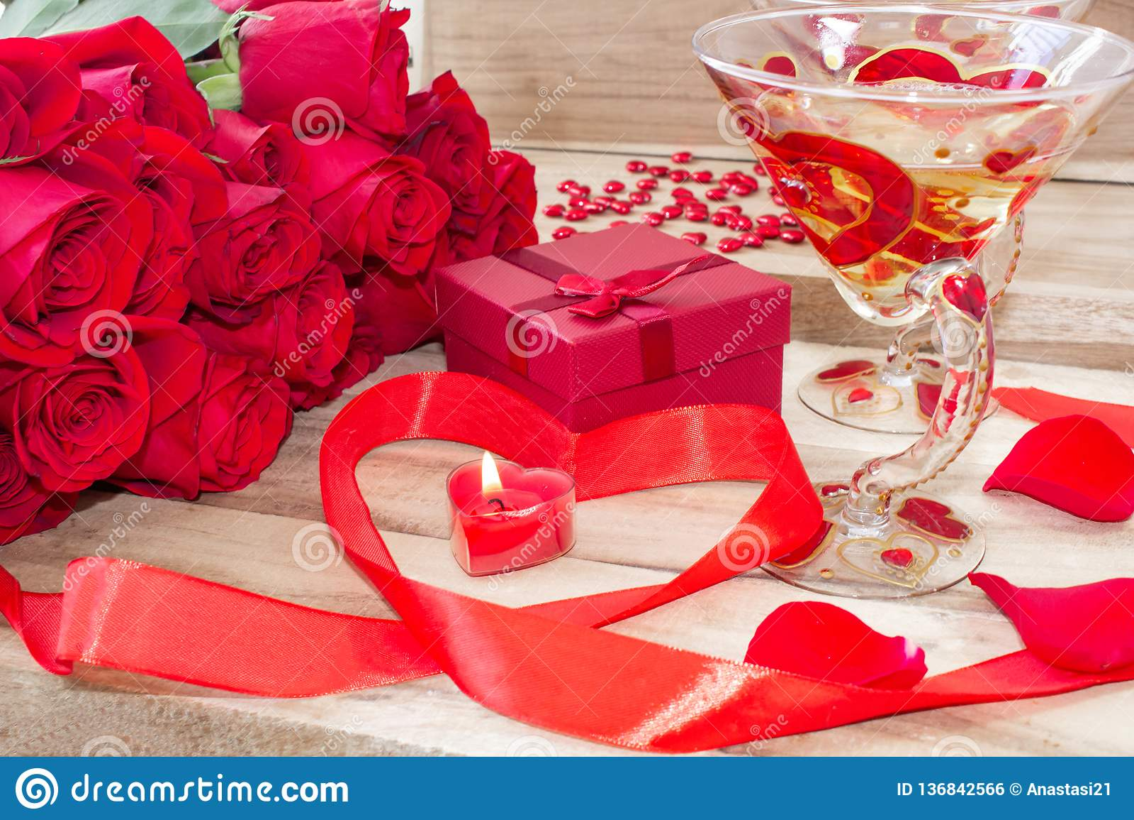Un uomo in una camicia tiene i fiori dei tulipani davanti al suo fronte e dà una scatola in forma di cuore su un fondo bianco
