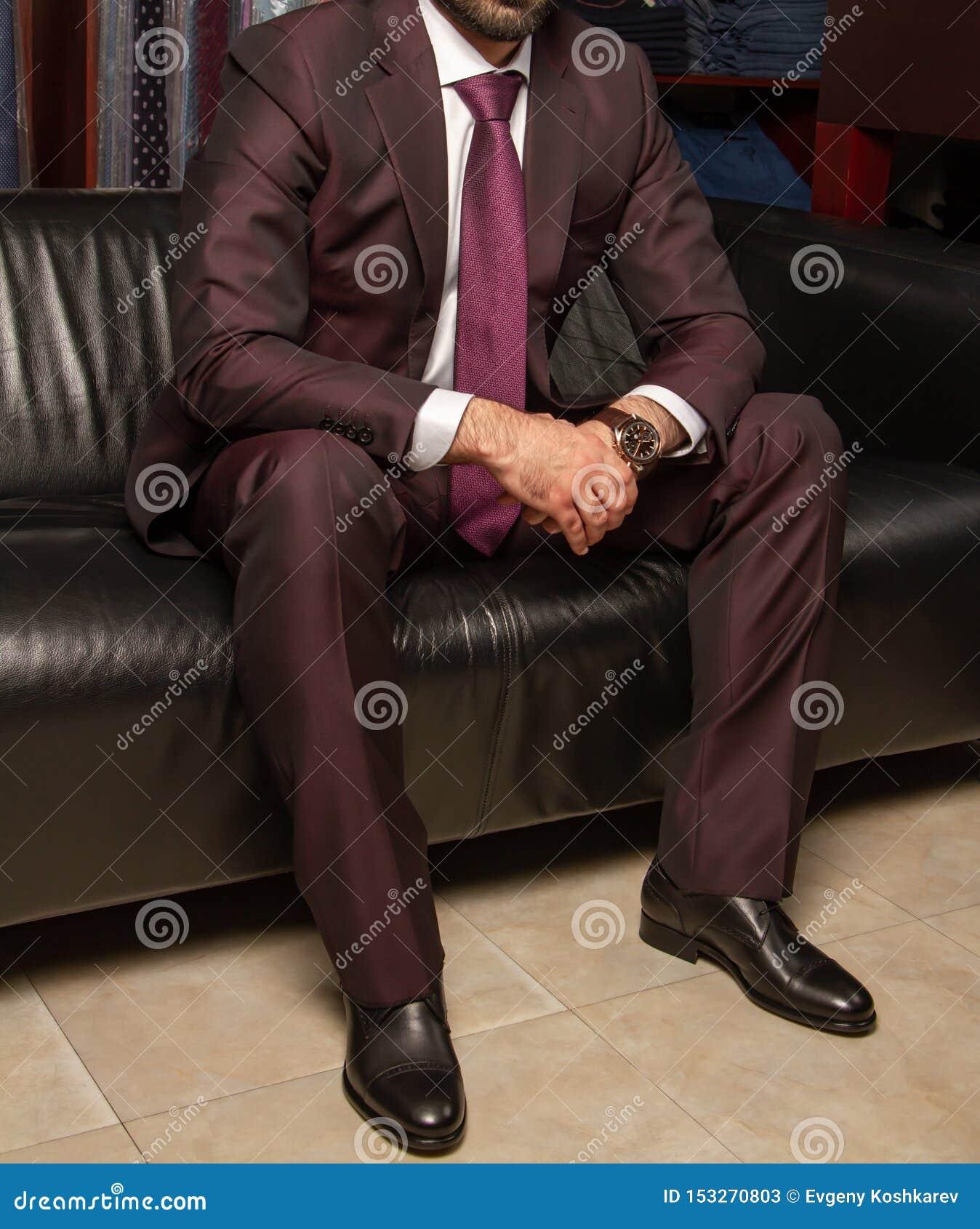 Un uomo in un vestito classico sta sedendosi su un sofà di cuoio nero, vista di parte di sinistra