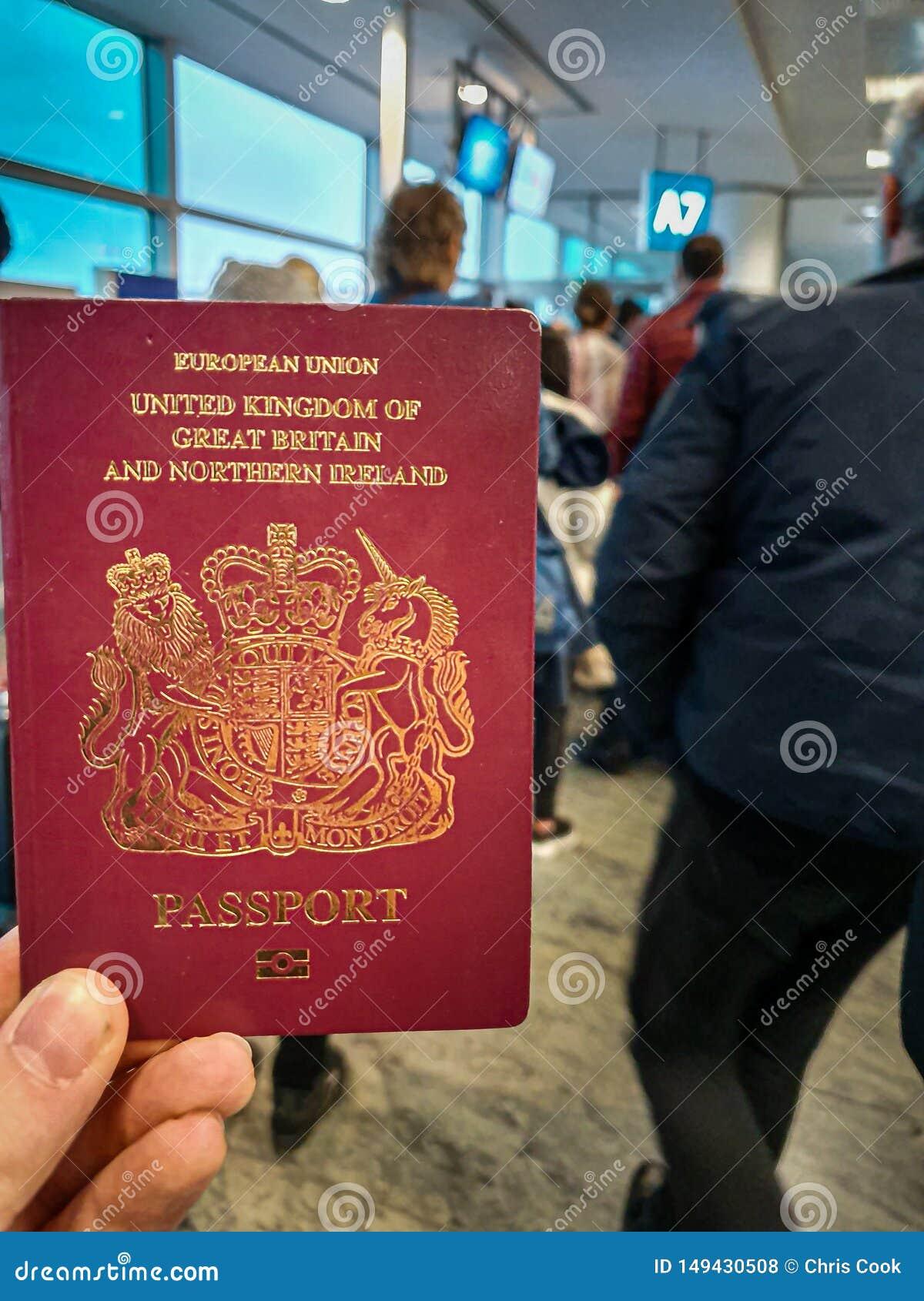 Un var?n blanco sostiene su pasaporte brit?nico rojo en su mano en el medio de un terminal apretado de la salida