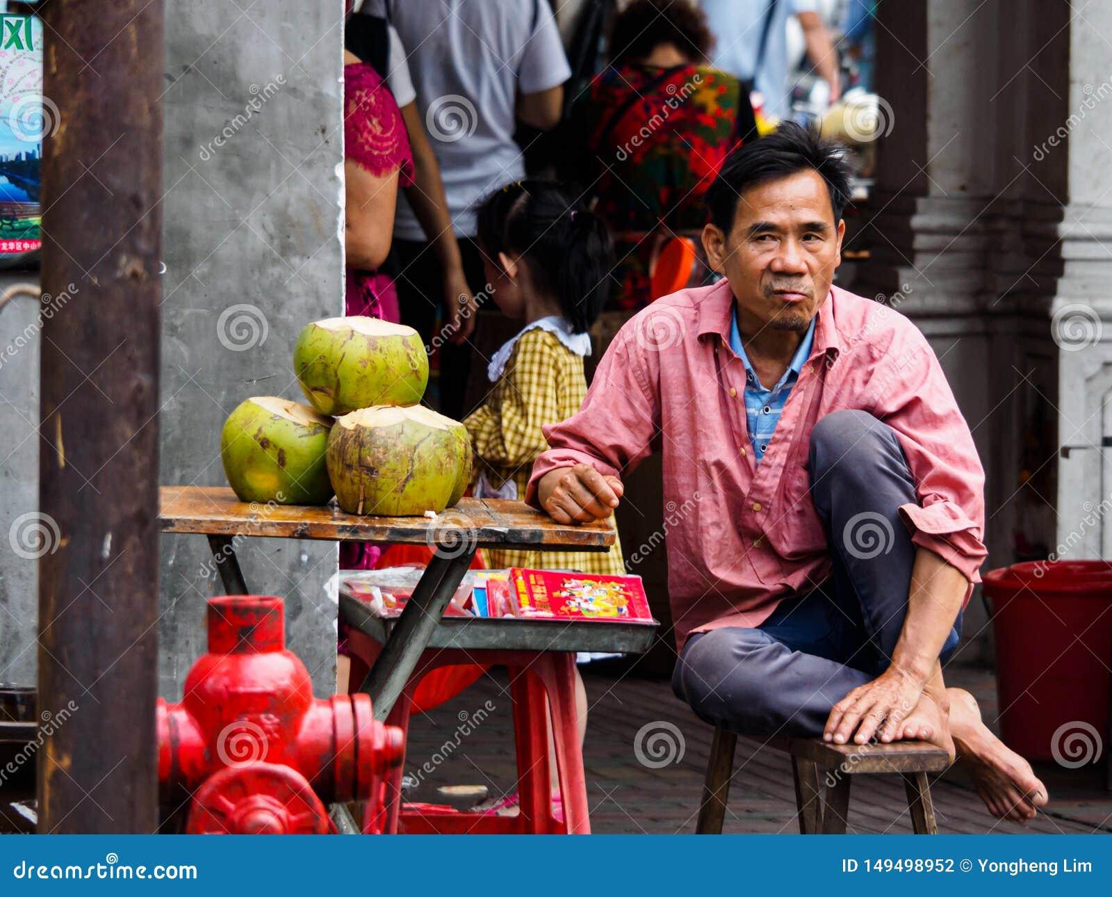 Un venditore ambulante che vende acqua di cocco