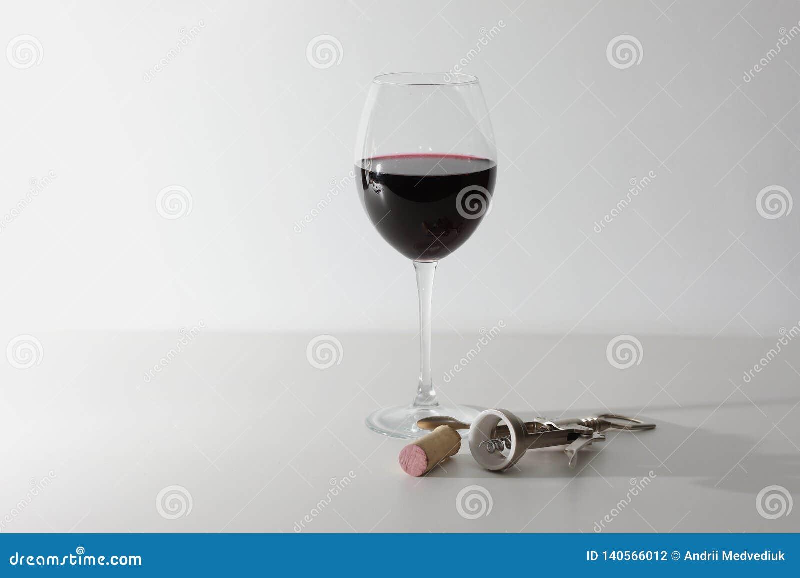Un verre de vin et de quelques outils de vin sur une surface en bois blanche Vin rouge