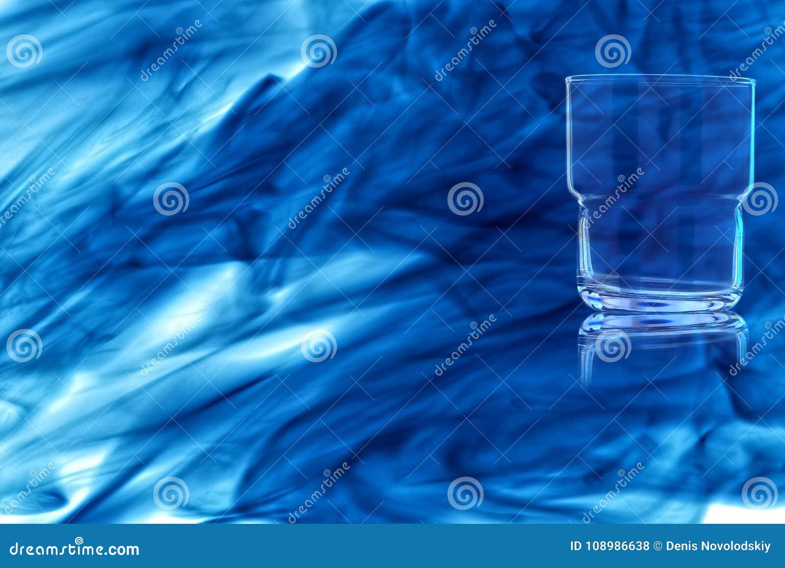 Un verre vide pour le whiskey enveloppé dans la fumée bleue