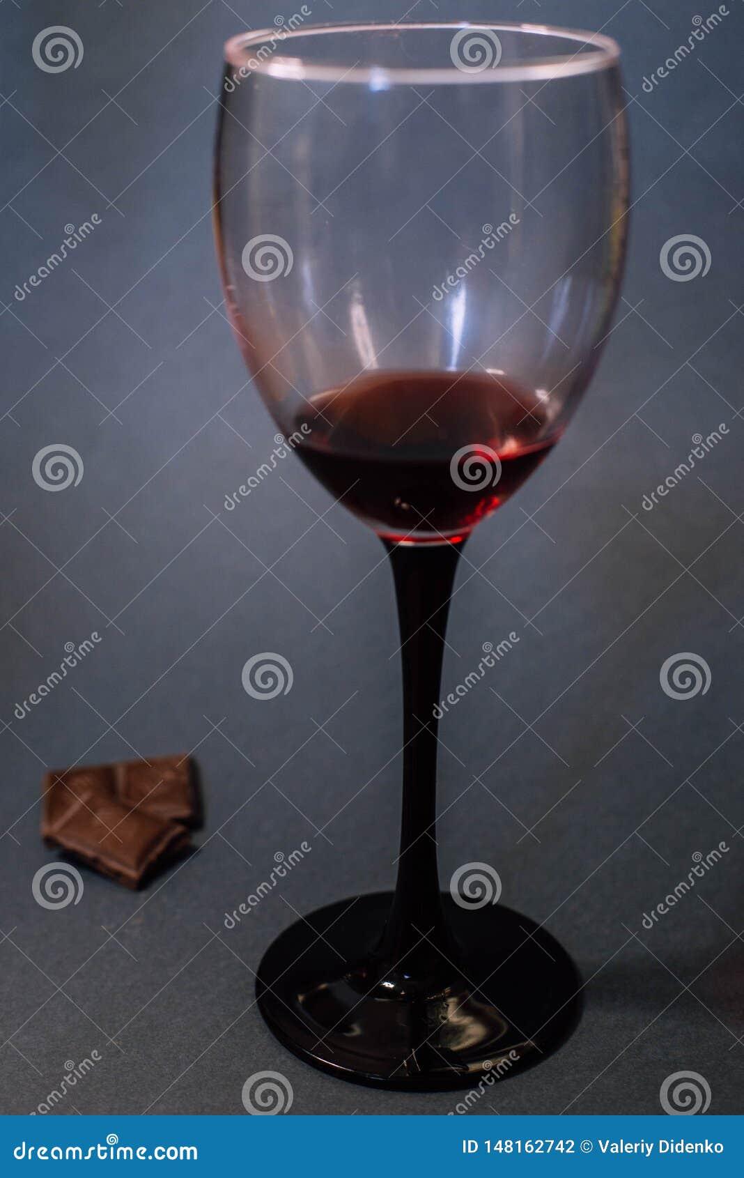 Un vetro delle fette del cioccolato e del vino rosso