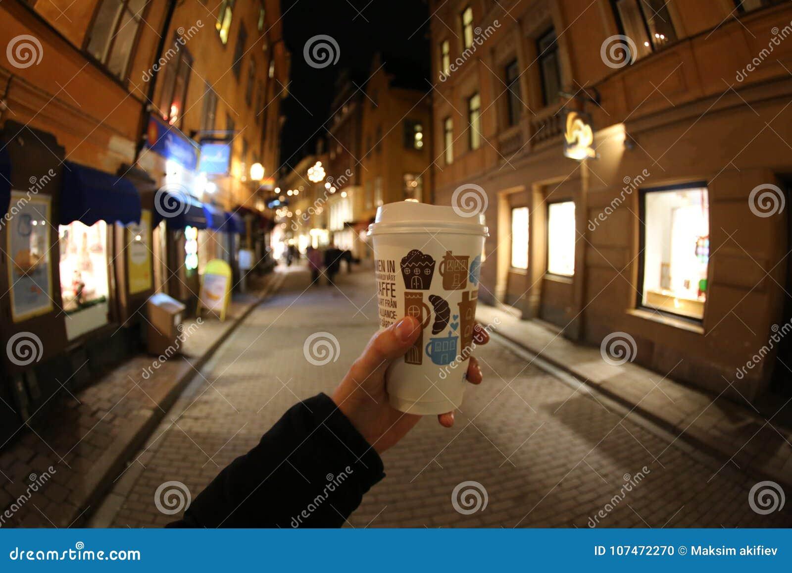 Un vetro di carta di caffè in una mano del ` s dell uomo in una via Stoccolma di notte