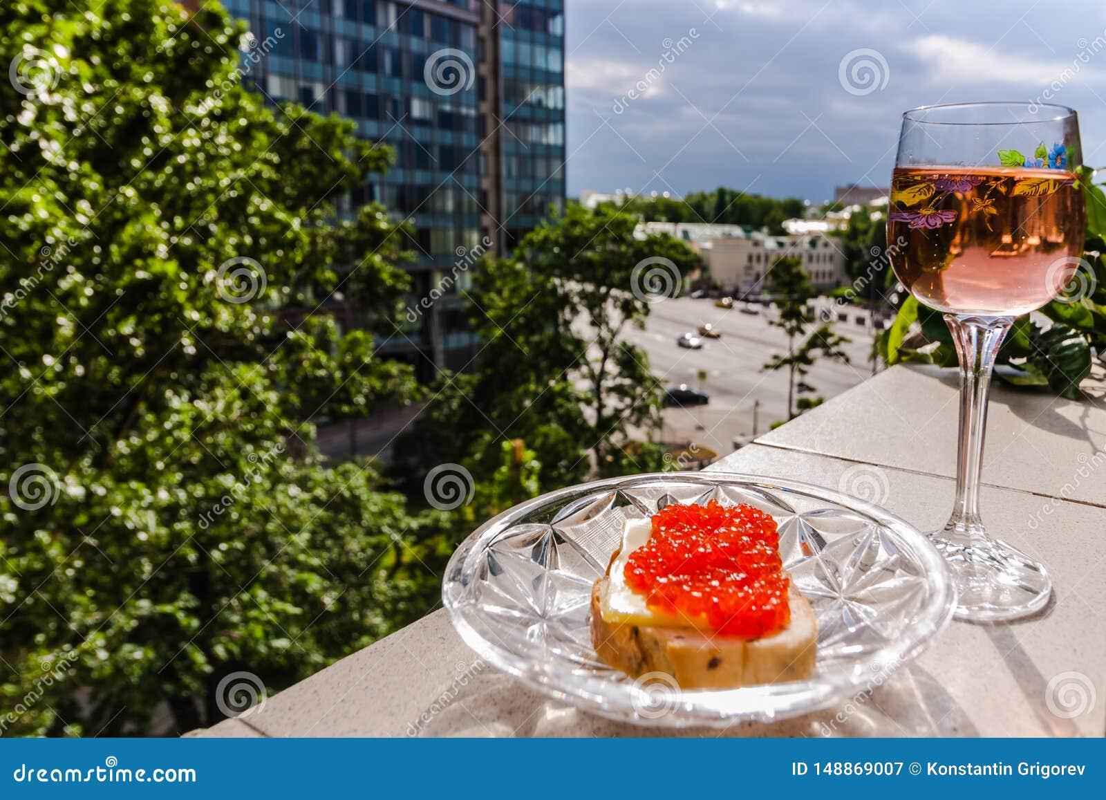 Un vetro di vino rosato e di pane con il caviale rosso sul parapetto