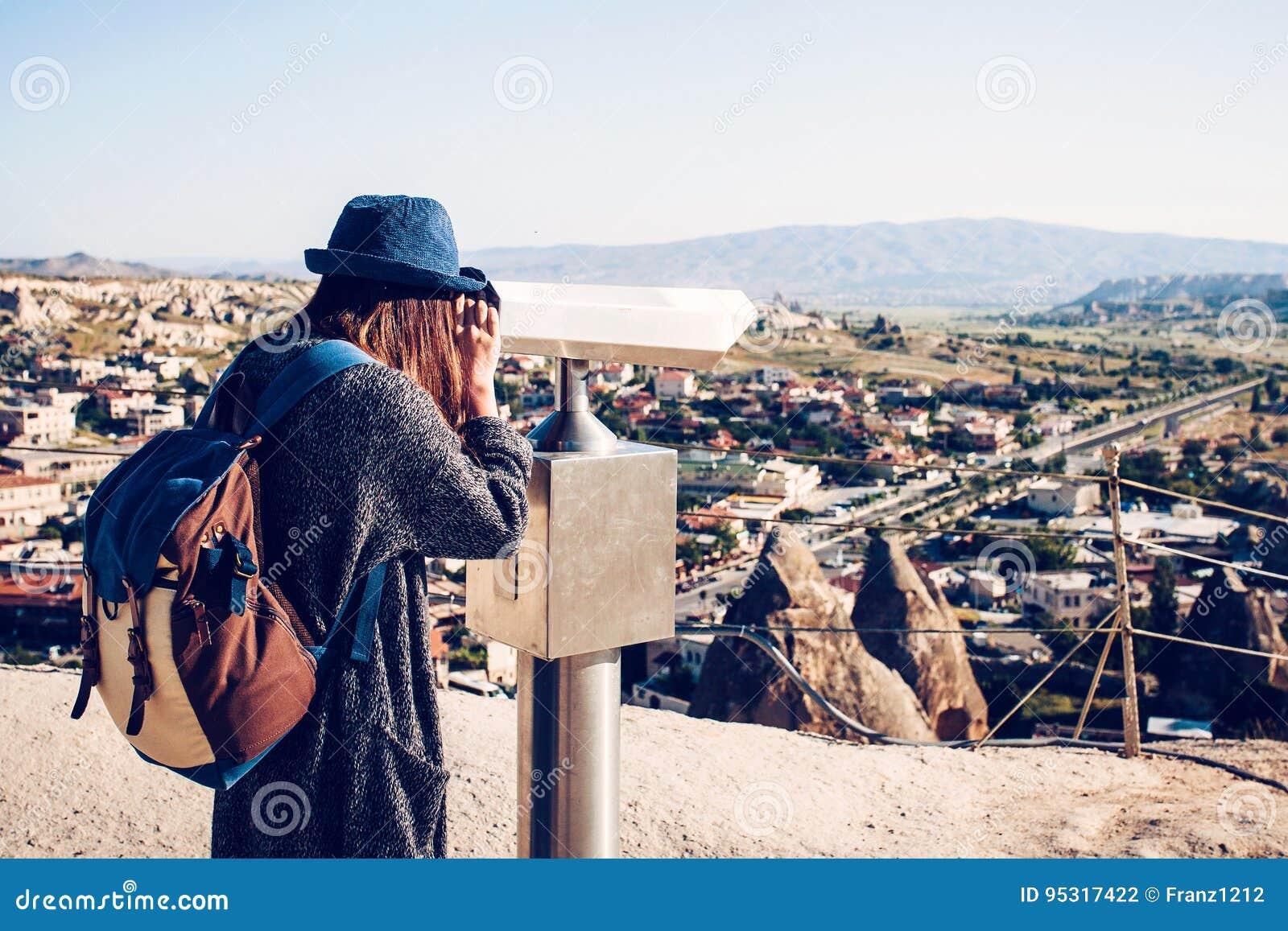 Un viaggiatore con uno zaino sopra al punto di vista osserva tramite il binocolo una bella vista della città di Goreme dentro
