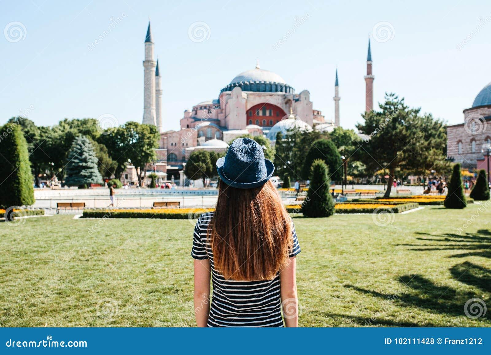 Un viajero de la chica joven en un sombrero de la parte posterior en el cuadrado de Sultanahmet al lado de la mezquita famosa de