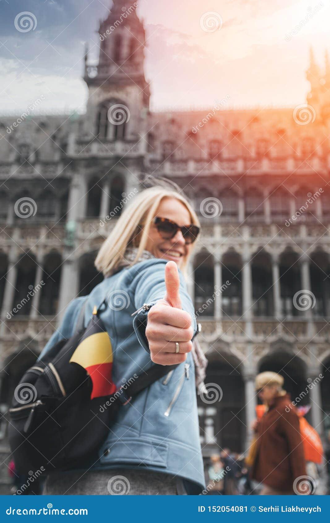 Un viajero femenino con una mochila y una bandera de Bélgica se coloca en el cuadrado de Grand Place en Bruselas y muestra sus pu