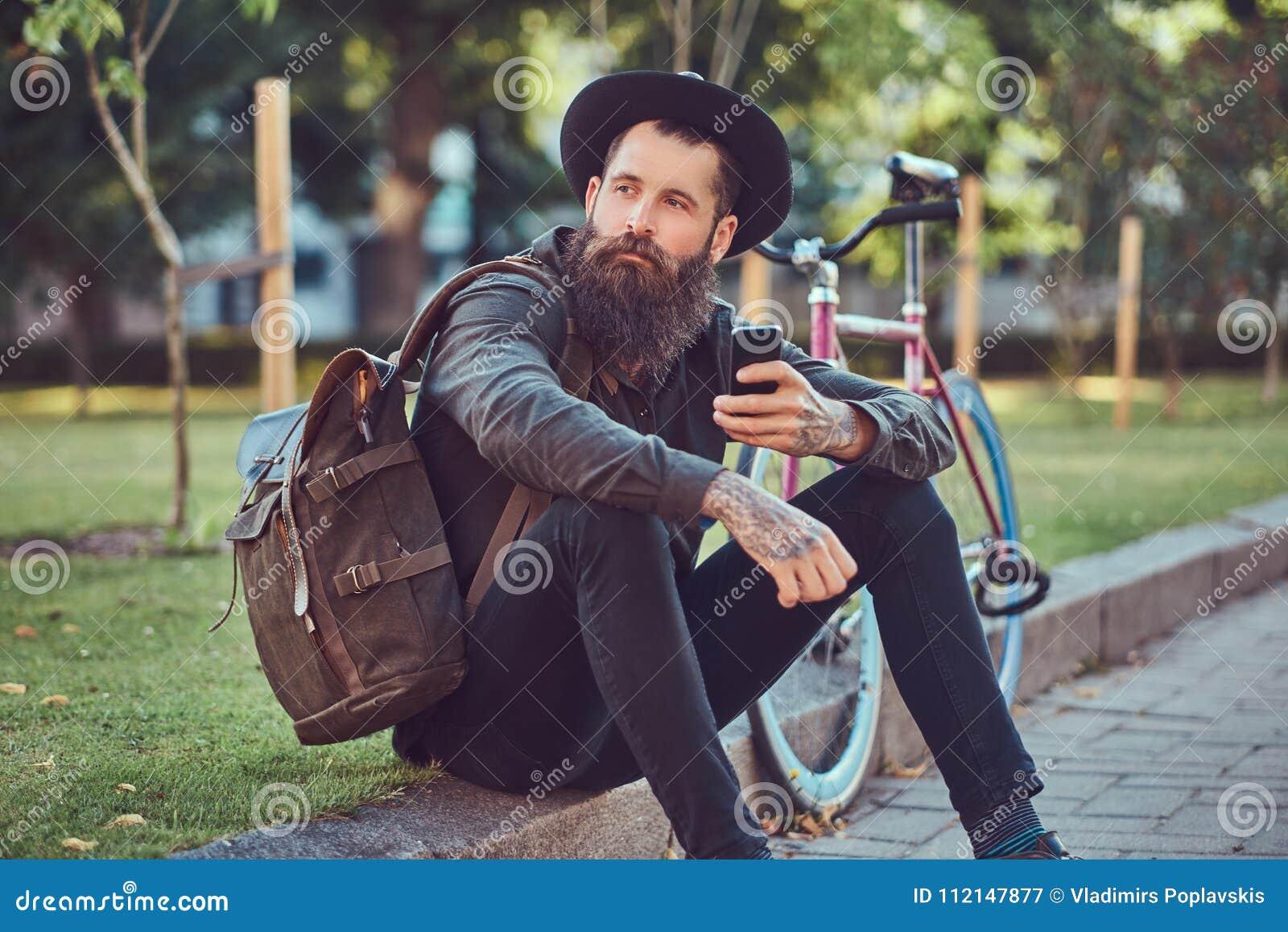 Un viajero hermoso del inconformista con una barba elegante y el tatuaje en sus brazos se vistieron en ropa casual y sombrero con