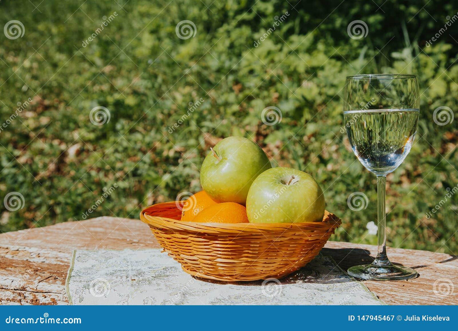 Un vidrio de agua y de las manzanas frescas de Apple en una cesta en una tabla de madera