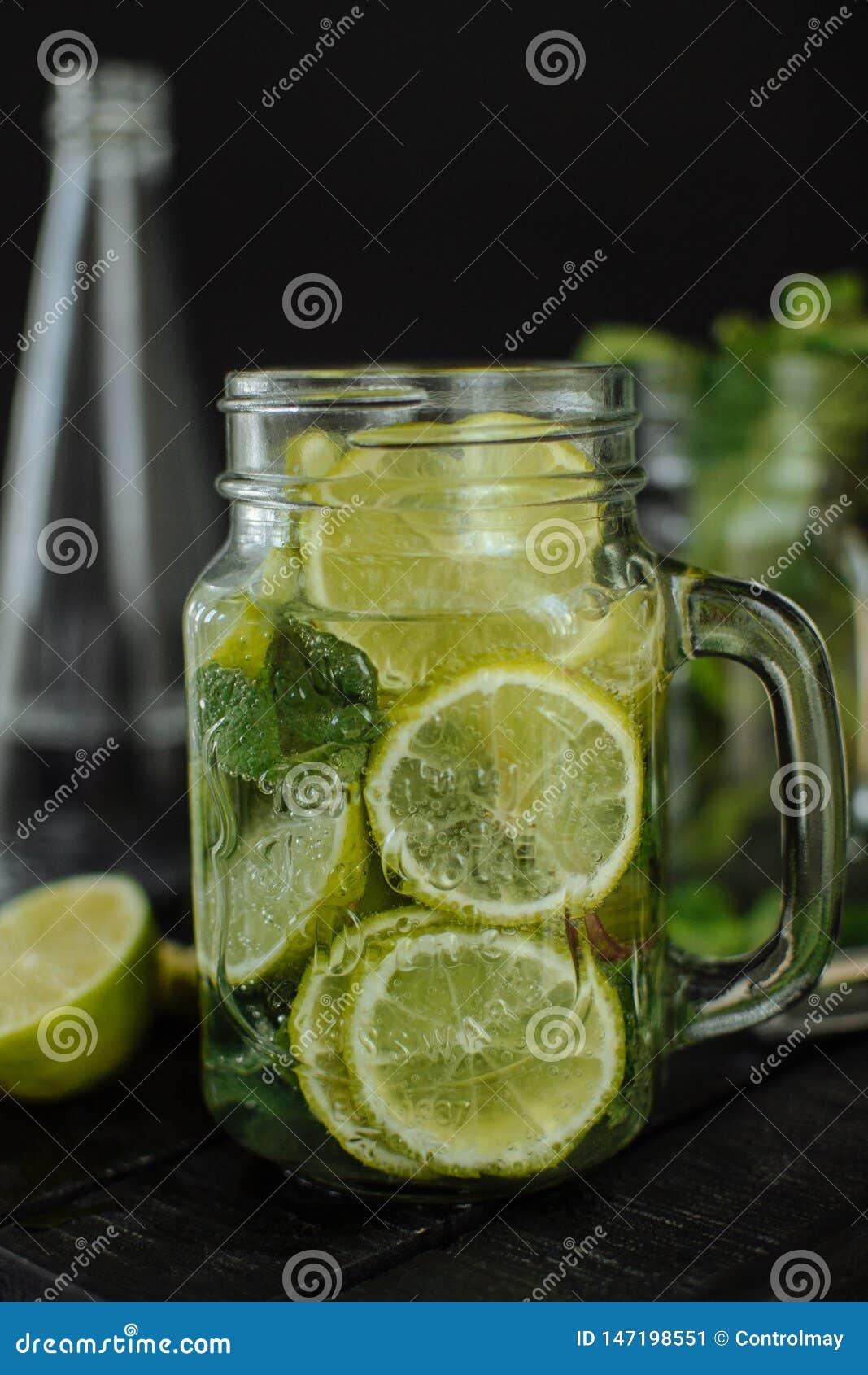 Un vidrio de limonada con la cal y el limón cortados en una taza en un fondo negro