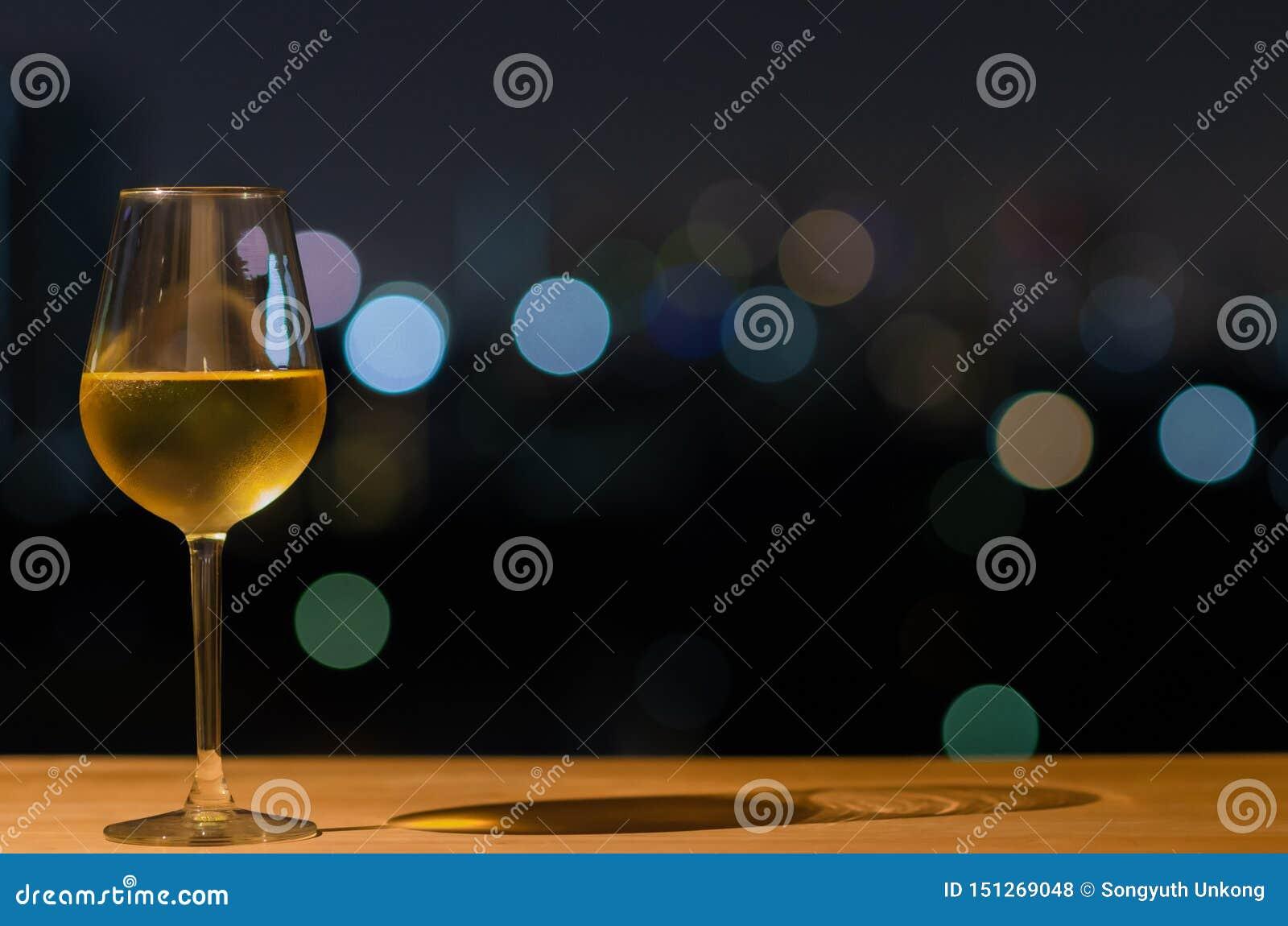 Un vidrio de vino blanco y de su sombra en la tabla de madera de barra del tejado con el bokeh colorido de la luz y del espacio d