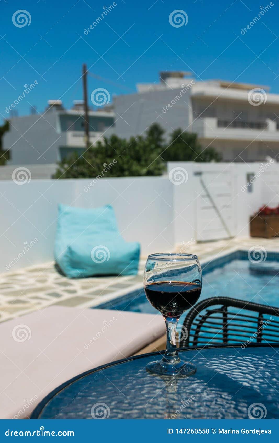 Un vidrio de vino tinto en la tabla por la piscina