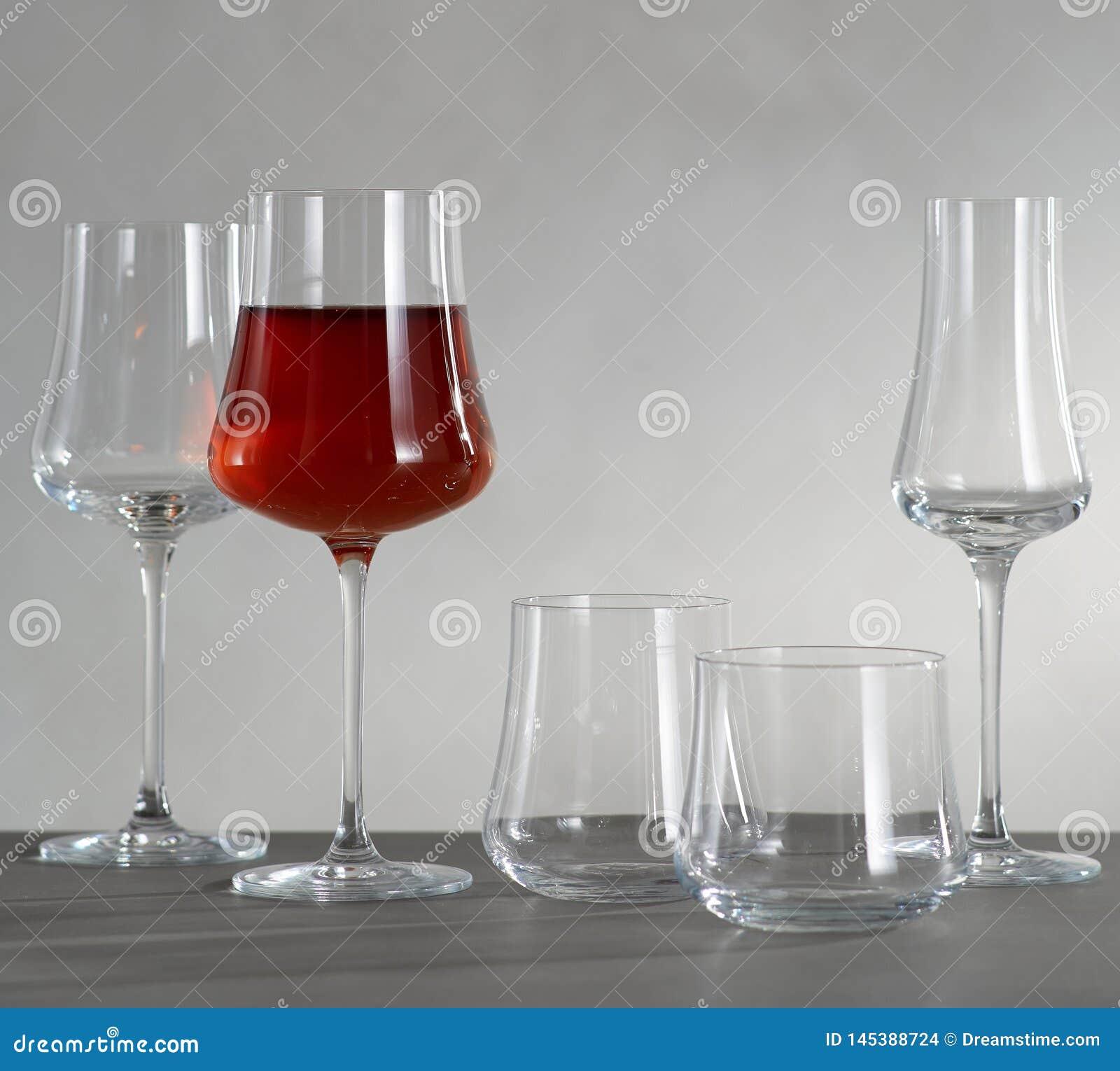 Un vidrio de vino tinto y de cuatro copas de vino vacías
