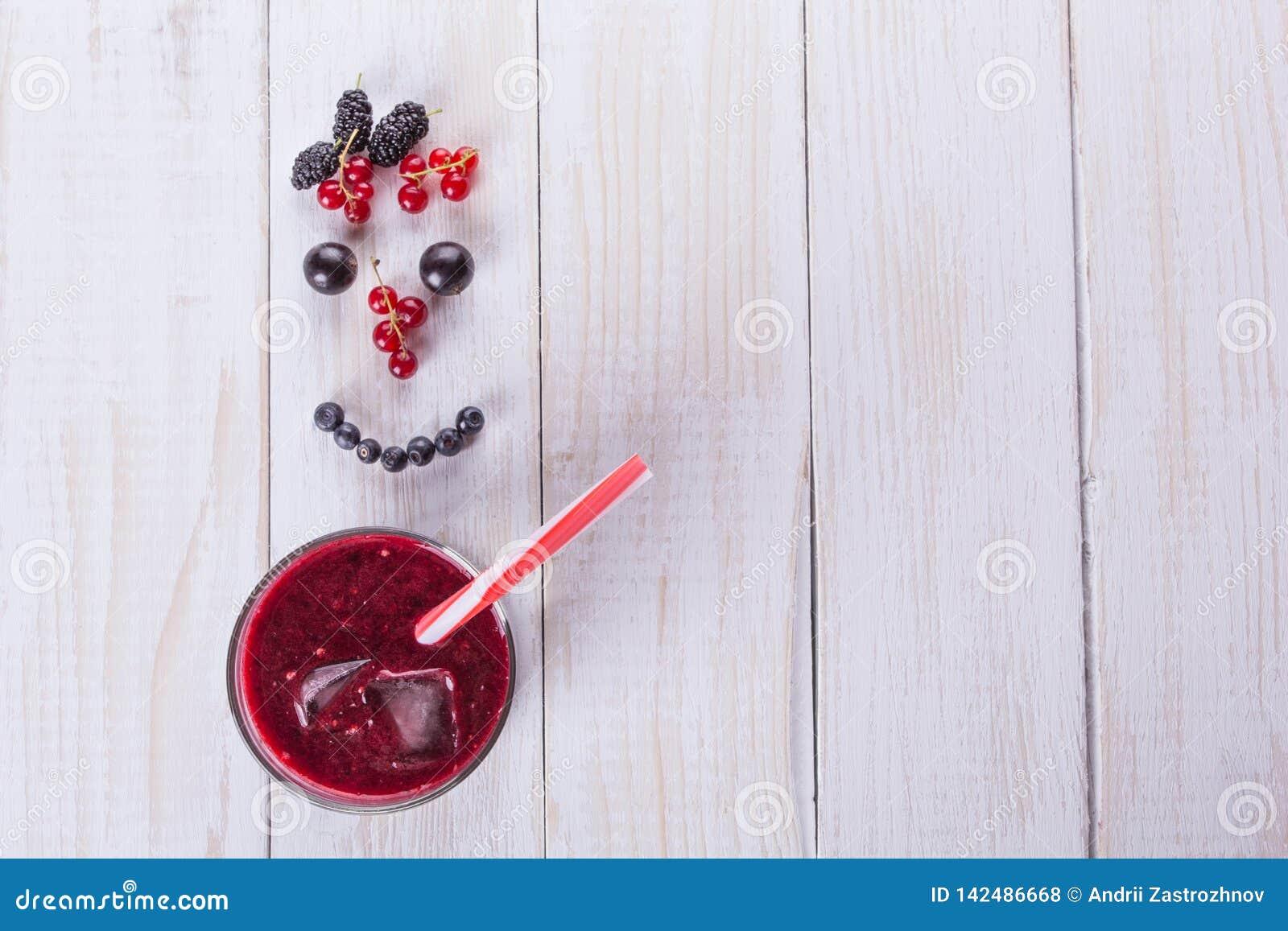 Un vidrio del smoothie de la baya en el fondo blanco Sonrisa de bayas Concepto de la comida de la dieta