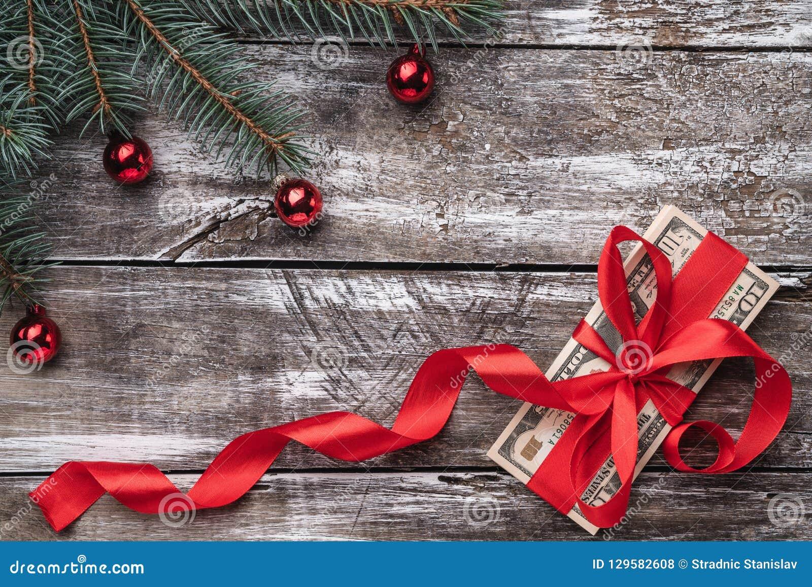 Un viejo fondo de madera de la Navidad, un árbol de abeto con las chucherías, dinero embellecido con la holgura roja