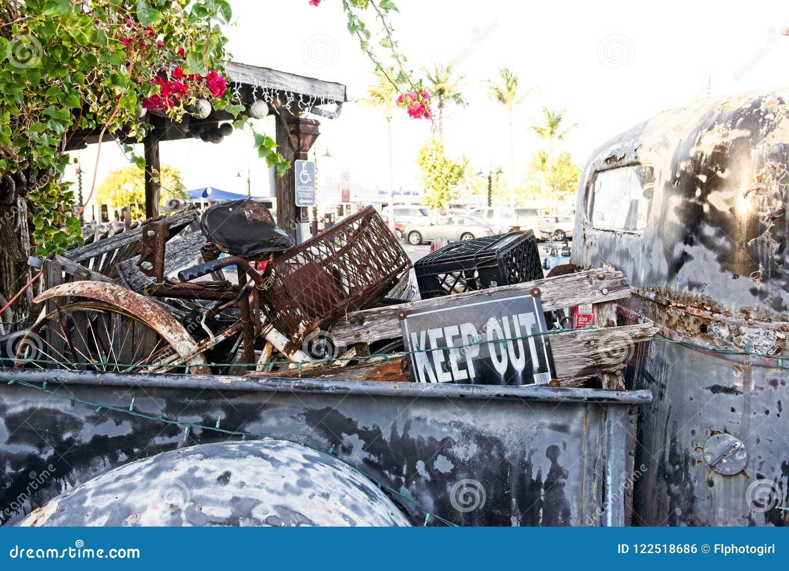 Un vieux camion rouillé avec le lit rempli d ordure se repose en dehors d un établissement dans la clé, la Floride occidentale Et
