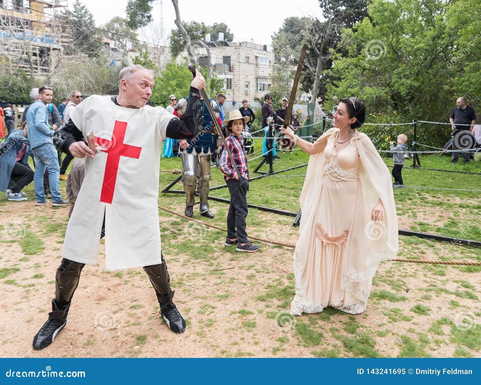 Un visitante vestido en un traje del cruzado y un visitante vestido en princesas de los trajes luchan con las espadas en el festi