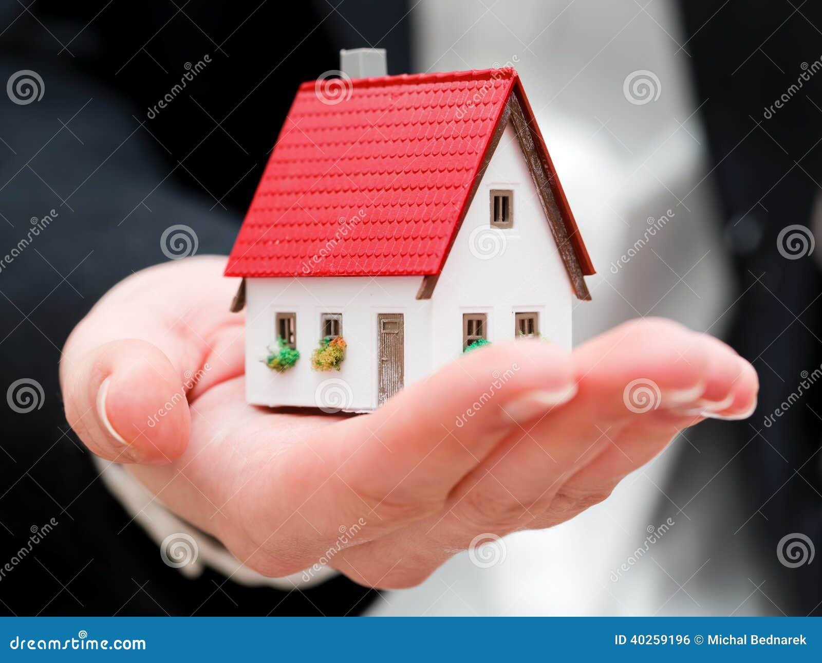 Un vrai agent immobilier tenant une petite nouvelle maison dans des ses mains