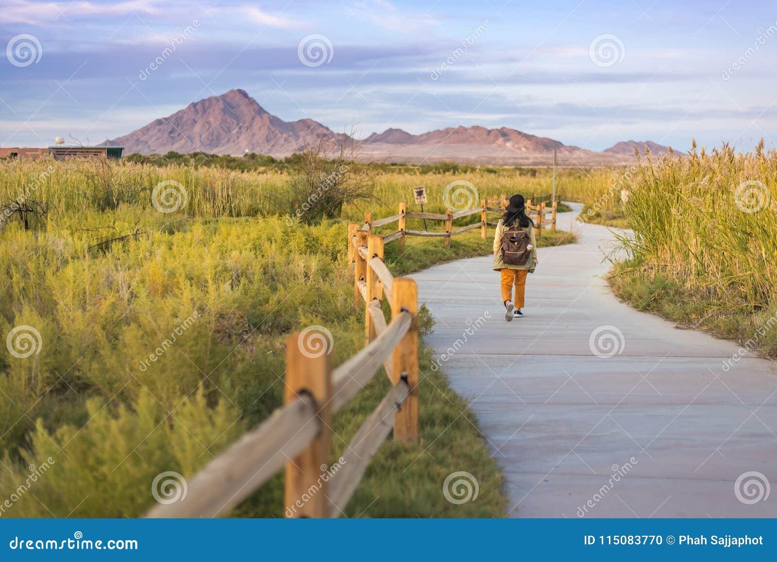 Un walkimg de la mujer en el rastro en humedales parquea Las Vegas