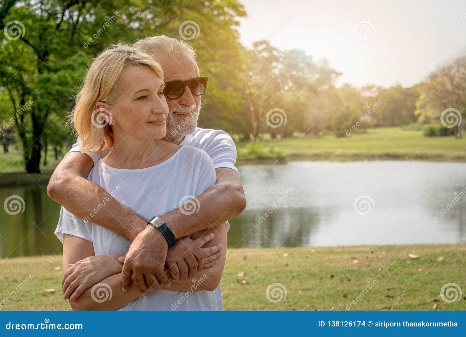 Una abrazo mayor mayor de los pares en un parque en tiempo de verano