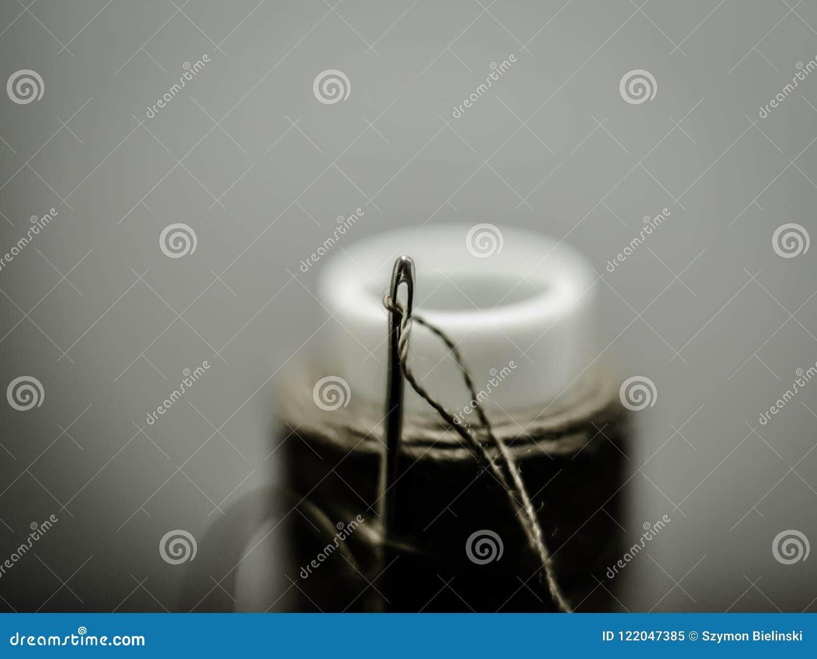 Una aguja de costura se pegó en un carrete del hilo en una escala macra