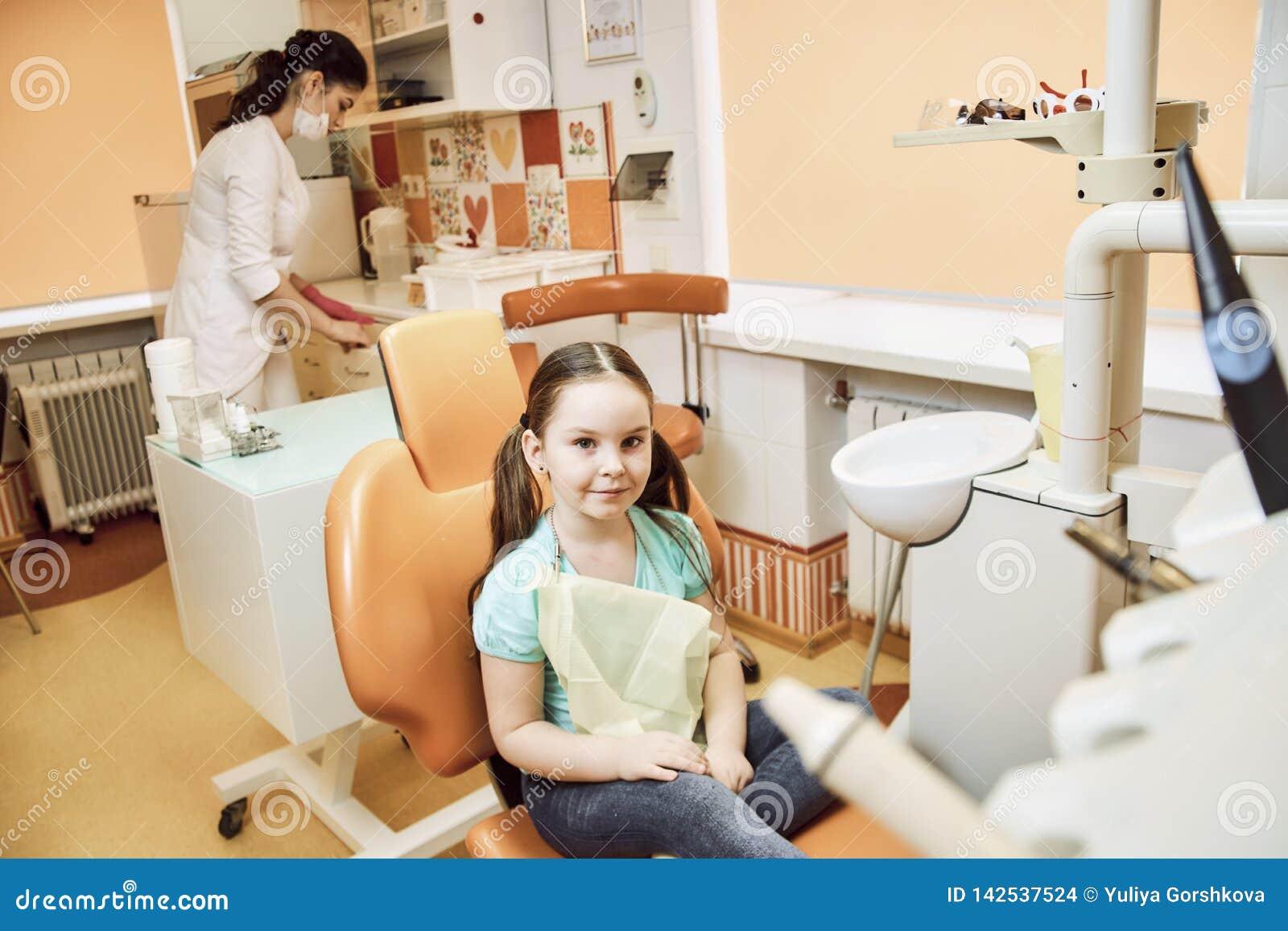 Una bambina che si siede su una sedia nell ufficio del dentista