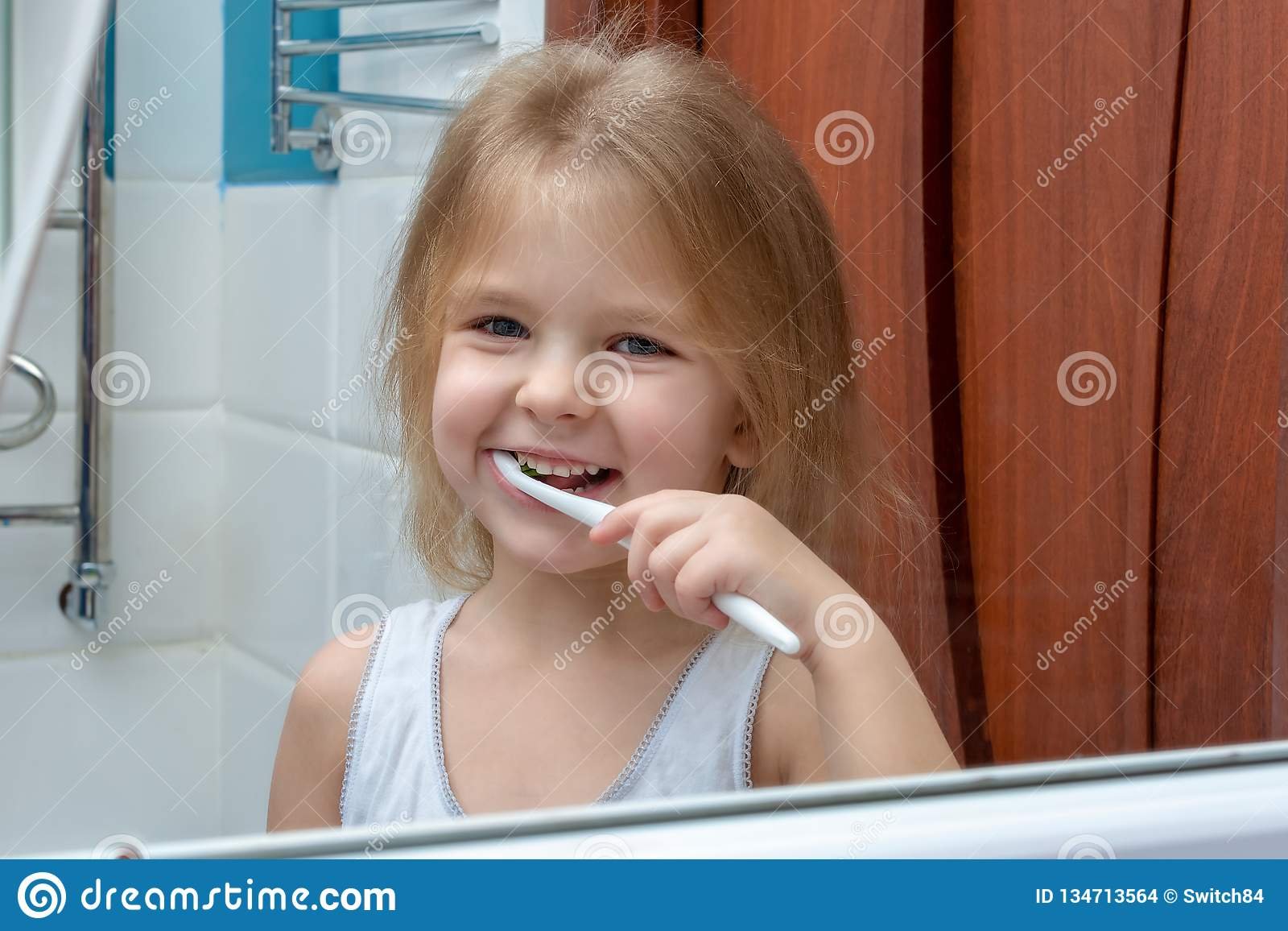 Una bambina con capelli biondi che puliscono i suoi denti Il bambino sta sorridendo alla riflessione nello specchio