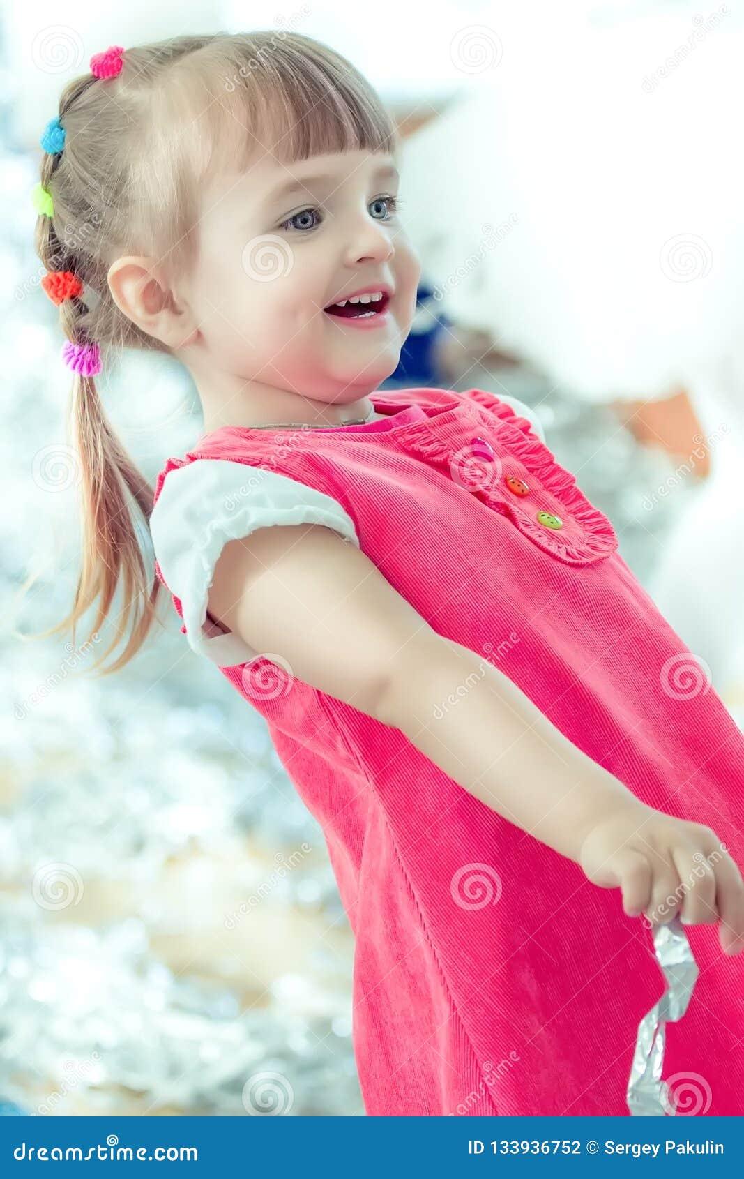 Una bambina con le risate delle trecce e divertiresi ad un partito dei bambini