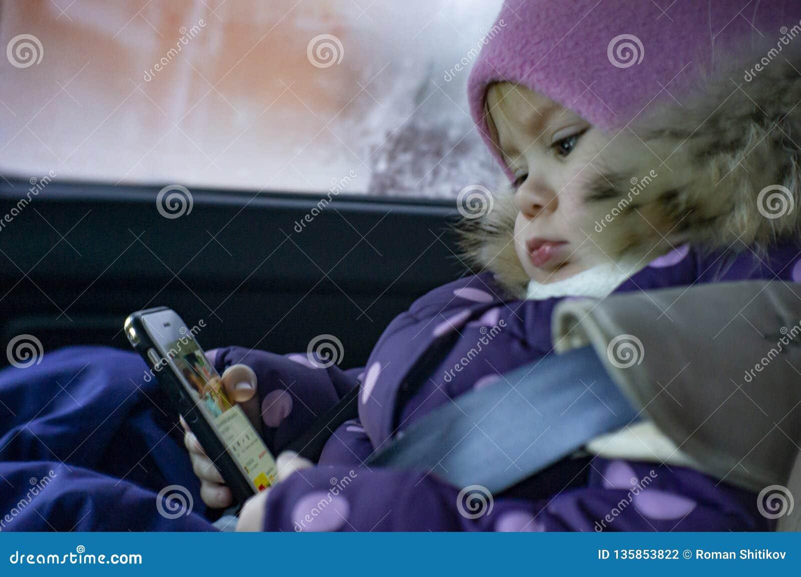 Una bambina gioca nel telefono mentre si siede in un automobile in un sedile del bambino