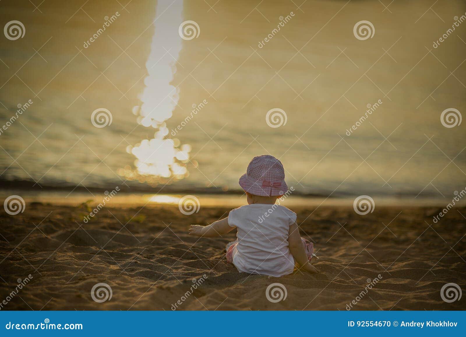Una bambina si siede sulla sabbia dal mare ed ammira il tramonto