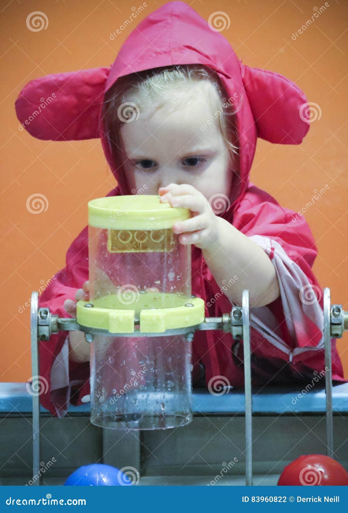 Una bambina sperimenta con acqua al ` s dei bambini di scoperta