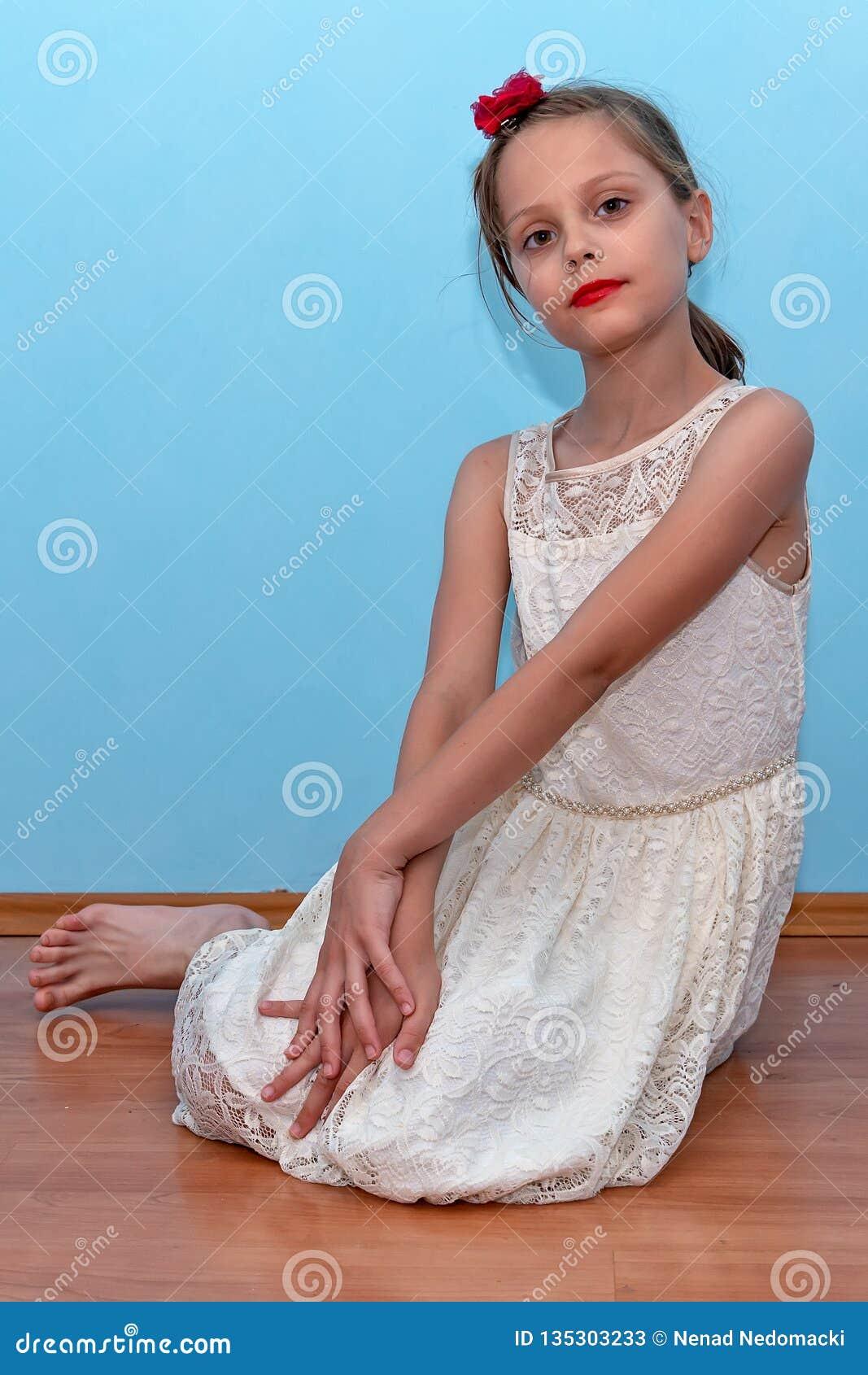 Una bella bambina posa la seduta sul pavimento